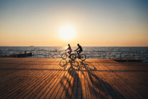 Couple of people cycling together at the beach at sunrise sky at wooden deck summer time