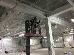 Worker treating steel beams with new decorative fire protection system used for the first time in the UK by Roseville Projects at 60 London Wall.
