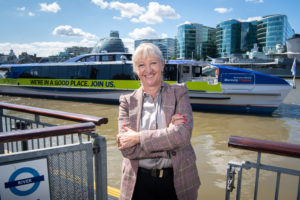 Thames Estuary Envoy Kate Willard OBE pictured at the launch of 'The Green Blue' action plan. Smiling with back to Thames and clipper boat visible behind.